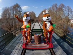 Two Easter Bunnies rides with a basket of colored eggs on a trolley over a bridge of Erlebnisbahn Templin-Fuerstenberg in northern Brandenburg Lychen, Germany. The 30-km rail stretch is part of the Easter Sunday attraction along which sweets will be hidden for a tourists ride on the old railway line.
