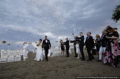 confetti wedding exit by the waterfront - For more beach wedding inspiration on WeddingWire!