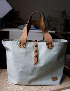 Pakowna, prosta torba z tkaniny technicznej w kolorze wyblakłej mięty ze skórzanymi rączkami.