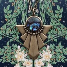 This Art Deco inspired pendant features a beautiful abalone shell infused stone, giving it a dreamy, oceanic quality. Background: Artist/Illustrator Walter Crane (wallpaper design - detail) 'Francesca' 1902