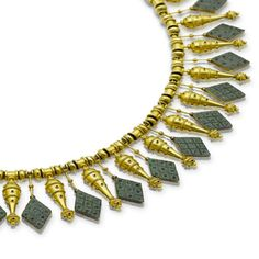 A rare gold and micromosaic necklace, by Castellani, circa 1875  Of archaeological revival design, the woven gold chain threaded with spherical and spool-shaped gold beads, suspending a fringe of lozenge-shaped micromosaic drops, alternating with amphorae of pierced and ropetwist decoration, maker's mark, length 40.1cm.