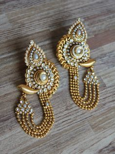 Golden long traditional earrings with polki and pearl work
