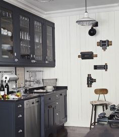 """""""Our family and friends visit us here often,"""" Thiergartner says, """"and they all have such fun, colorful personalities. I went with a mostly black-and-white palette so the house can serve as a background, letting people shine instead."""" In this photo: Honed black granite countertops and black-painted oak cabinets offer a dramatic counterpoint to the kitchen's white plank walls. Thiergartner bought the cabinet doors' nautical latches at a marine hardware store.  Bright idea: Plumbing-pipe…"""