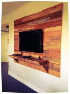 Reclaimed wood accent wall behind mounted TV. www.raw-design.org