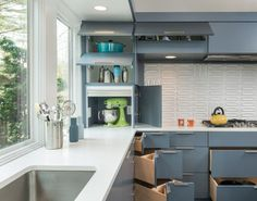 Creative storage behind grey painted cabinets and white solid surface countertops | Flavin Architects