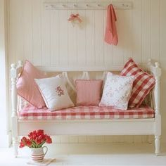 Red and white checked pillows, etc., on white bench for entry hall. Has an inviting/welcoming yet light feel to it.