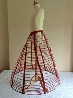 Thompson's Cage Crinoline, 1860s, in Snowshill Collection, quite bizarrely mounted backward on a youth mannequin. This crinoline is illustrated in Nancy Bradford's Costume in Detail. [jrb]