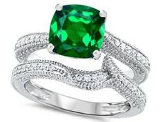 Cushion Cut Emerald Diamond Engagement Ring Wedding Set - A very unique color of a gemstone to die for atop of a vintage style shank comes this vibrant Cushion Cut Emerald Diamond Engagement Ring Wedding Set stamped in 925 Sterling Silver placed within a Prong setting featuring a huge Emerald Cushion cut center stone along with White Round cut accent stones around the shank and the matching band. The Cushion Cut Emerald Diamond Engagement Ring Wedding Set gemstones are simulated and all of…