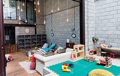 """Em vez de adotar o estilo """"brinquedoteca"""", o arquiteto Vitor Penha apostou na estética industrial chique para esta sala de brinquedos. Os móveis desgastados, os objetos de crochê e as arandelas antigas de cristal inspiram memória e poesia"""