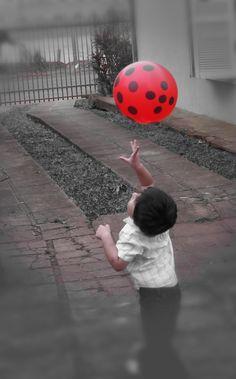 """""""Atrapando el Globo Rojo"""" es la fotografía de un niño, además de verlo como algo estético, al no mostrar el rostro intento que la persona que vea la foto, sienta las mismas ansías del niño para atrapar el globo.  La foto es de mi nene, la recorté y utilicé varios filtros para que quedará finalmente como se ve."""