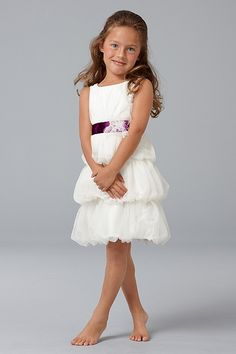 Ivory English Net knee length dress with jewel neck, shirred, bubbled skirt, smocked back, self flower and plum ribbon at empire.
