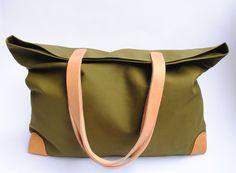 Große Tasche aus olivgrünem Markisenstoff mit Lederecken und Lederhenkeln; mit Druckknopf verschließbar. Futter aus altrosa Baumwolle mit Reißversc...