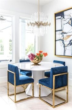 A round white dining table finished with gold and blue sapphire dining chairs under a brass and lucite chandelier.Get inspired by these dining room decor ideas! From dining room furniture ideas, dining room lighting inspirations and the best dining r Dining Room Paint Colors, Dining Room Design, Dining Room Furniture, Modern Furniture, Furniture Design, Furniture Ideas, Dining Room Blue, Modern Dining Rooms, Fine Furniture