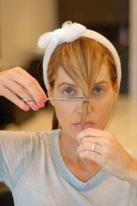 Twist your bangs into a single mesh in the center of your face above the bridge of your nose and snip the ends at an angle. Twisting the hair before cutting will give your bangs a wispy look....  i wonder if this works...i'm terrified to cut my own hair!!