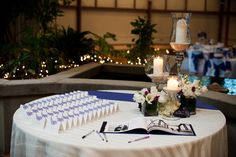 Small square vases of white tulips, lisianthus, roses, and a wrapped banana leaf displayed on the escort card table