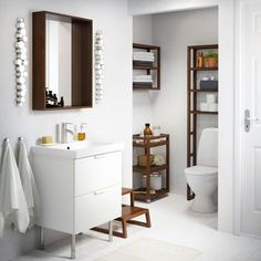 Bathroom with MOLGER trolley and shelves in dark brown and a GODMORGON wash stand cabinet in white.