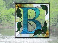 Need a great wedding gift? This piece will fit the bill! This 12 x 12 square stained glass monogram is in blue on clear with a multi-color