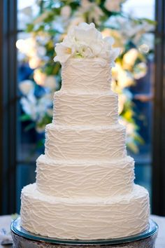 This is a beautiful cake. I'd add tiffany blue accents ( maybe blend it with the white) and coral ribbon/flowers?