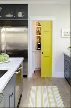 Fabulous gray kitchen with pop of color on pantry door.