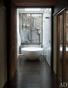 A Stan Bitters wall sculpture from Ten 10 is visible from the master bath. The tub and fittings are by Boffi; the walls and ceiling are sheathed in tile by Heath Ceramics.