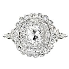 Art Deco diamond ring, composed of a central cushion-cut diamond weighing approximately 1.00 carats, surrounded by two-tiers of smaller circular-cut diamonds, with a scalloped edge, and partway diamond-set shanks, mounted in platinum, the ring from the top measuring approximately 14mm in length and 13mm in width, circa 1920.