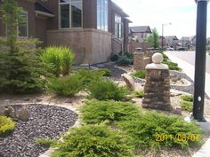 Xeriscaping a front yard with two contrasting decorative rocks.