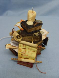 candle formed from polymer clay with a candle body centre into which is inserted a replaceable 50ma bi-pin candle flame bulb. The wires for the candle bulb holder run up the centre of the book stack A two pin plug is attached at the bottom end to connect to a 12volt power source