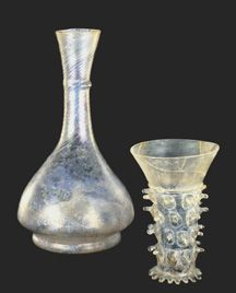 Bottle (14th-15th Century). Probably northern Italy. Glass, gather inflated in dip mold, withdrawn and blown to final shape and size. H. 22.7 cm (8.9 in.); Diam. (max.) 12.6 cm (5 in.).   Also: Beaker Decorated with Prunts (13th-14th Century). Northern Italy, Switzerland or southern Germany. H. 12.5 cm (4.9 in.); Diam. (rim) 8.4 cm (3.3 in.).