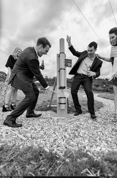 Black and white photo of wedding guests playing splat the rat at their friends…