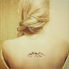 Small upper back tattoo of a mountain range on Lu.