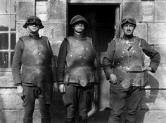 1914-1918:Body armor of the First World War: 1918 Exhibiting pock marks and bullet holes, three members of the Ordnance Department demonstrate the effects of pistol, rifle and machine gun fire upon body armor, during testing at Fort de la Peigney, Langres, France. (U.S. Army photo)