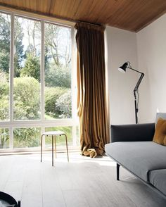 Home renovation update. Muuto outline sofa. 70s home renovation project. Oversized window with garden view. Ochre velvet curtains