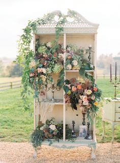 Vintage armoire used as wedding ceremony decor with vintage candlesticks and stunning florals by Holly Heider Chapple Flowers, Ltd. Image by Jodi Miller Photography at Shadow Creek in Purcellville, VA.