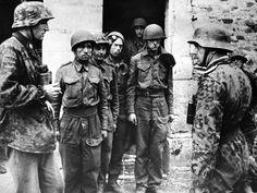 Parachutistes britanniques de la 6e Airborne division tombés derrière les lignes allemandes. Leurs visages graves témoignent de leur anxiété ils sont gardés par des éléments SS de la 12e Panzer Division. Juin 1944.