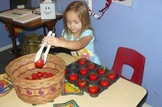 have a basket of apples, muffin tin and tongs to be able to transfer the apples back and forth.