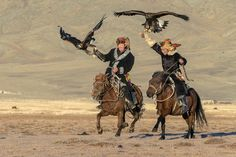"""Kazakh eagle hunters galloping across the steppes with their eagles held high. I was staying at a ger with some Kazakh herders in Western Mongolia and the local eagle hunters were preparing to participate in the eagle festival. Our host and his friend were showing off for the camera when I caught them galloping towards me with their eagles held high."" Picture: Terry Allen"