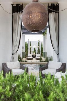 Mediterranean style patio features a small sitting space filled with a pair of wicker chairs placed atop white and gray cement tiled floors illuminated by a large copper pierced lantern finished with white outdoor curtains with black trim.