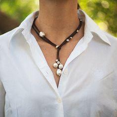 Conjunto de collar y pendientes. Cordón de piel y perlas de Mallorca. Piezas en rodio satinado y plata con efecto envejecido. Nudo corredero en