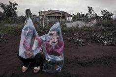2014: The Year in Volcanic Activity - In Focus - The Atlantic   Two boys wear plastic bags to cover their face from ash following a further eruption of Mount Sinabung on January 4, 2014 in Karo District, North Sumatra. (Ulet Ifansasti/Getty Images)