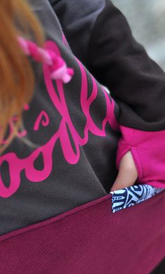 Detail of the hoodie pocket - black and white pattern. Pink handmade cord in the hood. Let's dooodle logo
