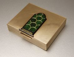 An Art Deco 14K yellow gold, jadeite, enamel and diamond cigarette case, by Cartier, Signed Cartier, circa 1925 London, 14K yellow gold topped with a shield-shaped plaque set with carved jadeite tablets, surrounded by green and black enamel, terminating with a bar of 34 rose-cut diamonds.