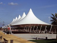 Tensile fabric structures are most often used as roofs as they can economically and attractively span large distances. Fabric Structure, Shade Structure, Membrane Structure, Tensile Structures, Experience Center, Canopy Design, Hanging Plants, Textiles, Santorini