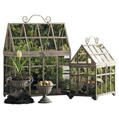 Two metal terrariums shaped like greenhouses with latticed glass sides.  Product: Small and large terrariumConstruct...