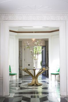 Gilded - A round glass-topped table with a pair of green chairs