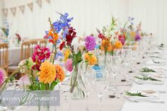 Multi coloured flowers in jars scattered along wedding tables. Summer wedding.
