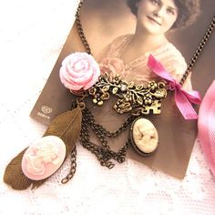 Sautoir camée Au temps Jadis orné d'un assemblage de camées, d'une plume et d'une exquise rose pailleté ,il   rapelle le charme et la grâce des bijoux d'antan. Un brin de nostalgie pour un bijou sautoir unique- 25 euros