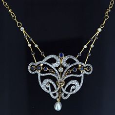 A sparkling, show-stopping necklace (1895-1915)  composed of 18 karat yellow and white gold and studded with 2.25 carats of white diamonds accented with deep blue sapphires. The elaborate flowing design, reminiscent of the late Victorian and early Art Nouveau transitional jewelery, was lovingly produced in the late 20th century. An impressive, dressy necklace.