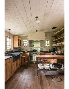 Architecture firm Pearson Design Group and interior decorator Kristen Panitch used traditional cabinetry, antique lighting fixtures, and hinged windows to make the kitchen of a newly built lakeside compound in upstate New York look as if it's been there for generations.
