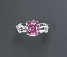 A PINK SAPPHIRE AND DIAMOND RING, BY MAUBOUSSIN  Centering upon a cushion-cut pink sapphire, weighing approximately 3.29 carats, to the 18k white gold tapering band enhanced by circular-cut diamond trim, with French assay mark and maker's mark, in a Mauboussin purple leather case and box Signed Mauboussin (indistinct), no. A8910 54