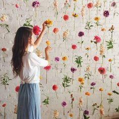 吊るされた小さなガラス瓶と一緒にお花を飾ってつくるフラワーウォール。